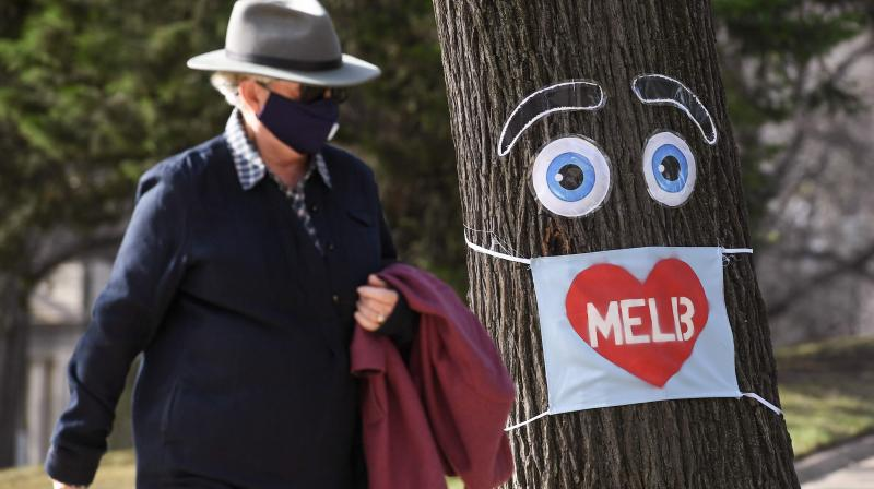 A man walks past a large face mask pinned to a tree in Melbourne on August 3, 2020 after the state announced new restrictions as the city battles fresh outbreaks of the COVID-19 coronavirus. (AFP)