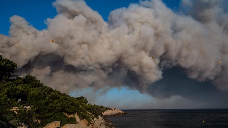 A picture taken on August 4, 2020 shows three Canadair bomber planes of the French Securite Civile flying past a column of smoke, as wild fires broke out in La Couronne, near Marseille. (AFP)