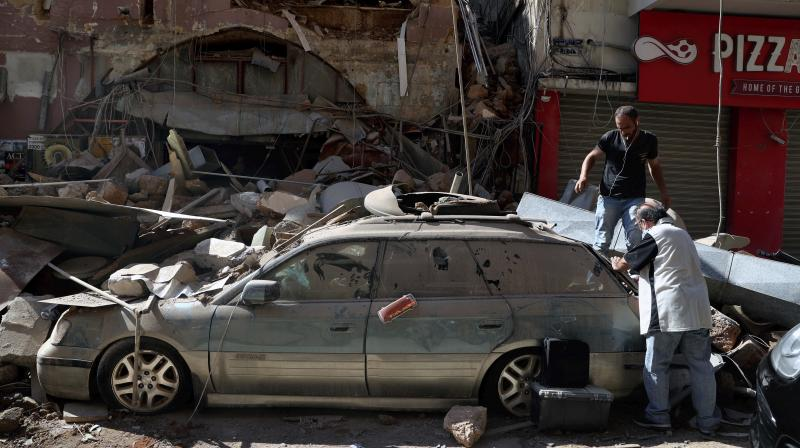 People inspect their car that was damaged in Tuesday's massive explosion in the seaport of Beirut, Lebanon, Wednesday, Aug. 5, 2020. (AP)