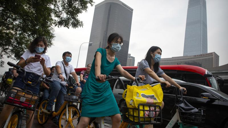 People wearing face masks to protect against the coronavirus wait at an intersection in the central business district in Beijing. (AP)