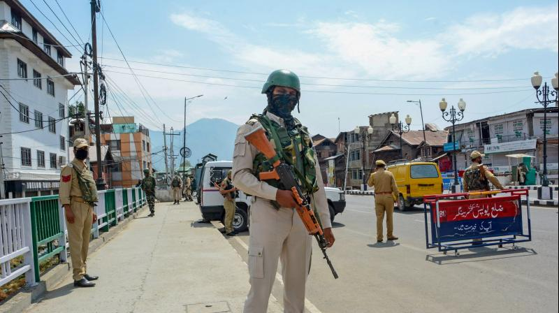 A CRPF jawan stands guard along a street on the first day of the two-day curfew in Srinagar, Tuesday, Aug. 4, 2020. (PTI)
