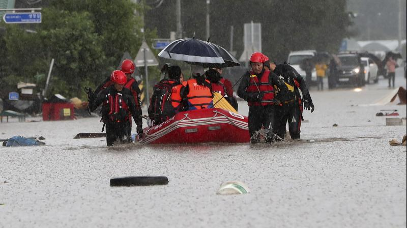 Rescue workers evacuate residents on a rubber boat in Cheorwon, South Korea. (AP)