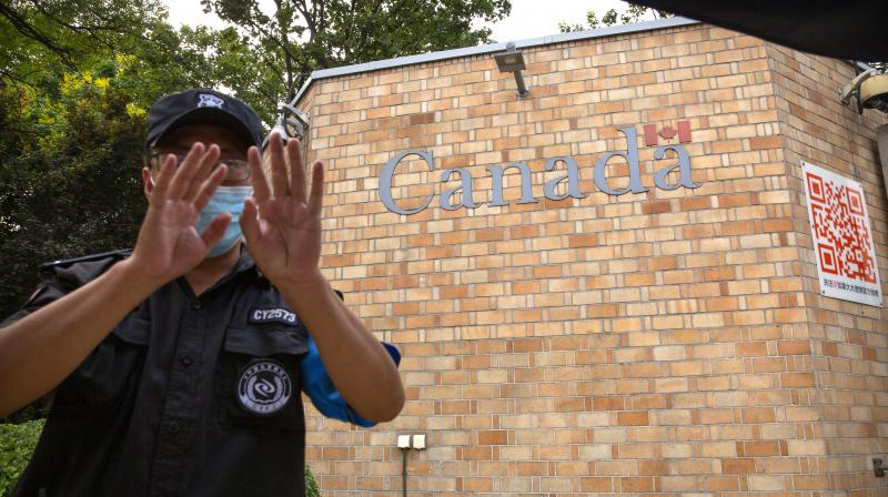 A security officer wearing a face mask to help protect against the coronavirus gestures outside the Canadian Embassy in Beijing. (AP)