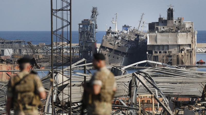 Lebanese army soldiers stand guard in front of destroyed ships at the scene where an explosion hit on Tuesday the seaport of Beirut, Lebanon. (AP)