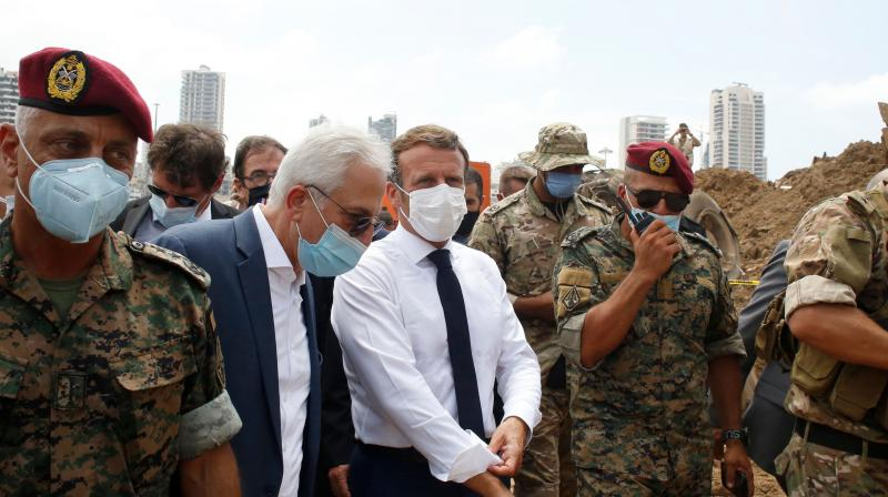 French President Emmanuel Macron (C) visits the devastated site of the explosion at the port of Beirut, on August 6, 2020 two days after a massive explosion devastated the Lebanese capital in a disaster that has sparked grief and fury.(AFP)
