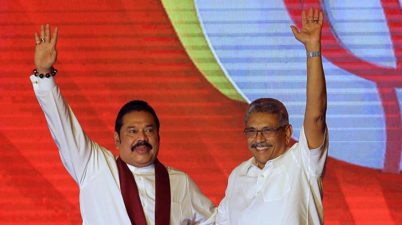 Sri Lankan President Mahinda Rajapaksa, left, and former Defense Secretary and his brother Gotabaya Rajapaksa wave to supporters. (AP)