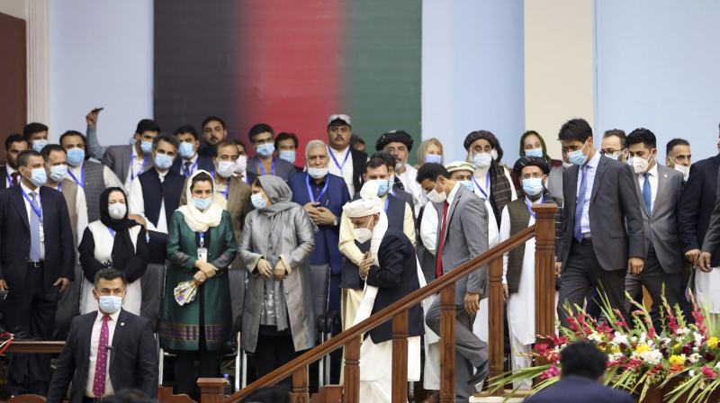 Afghan President Ashraf Ghani, center, wearing a protective face mask to help curb the spread of the coronavirus, arrives for an Afghan Loya Jirga meeting in Kabul, Afghanistan. (AP)