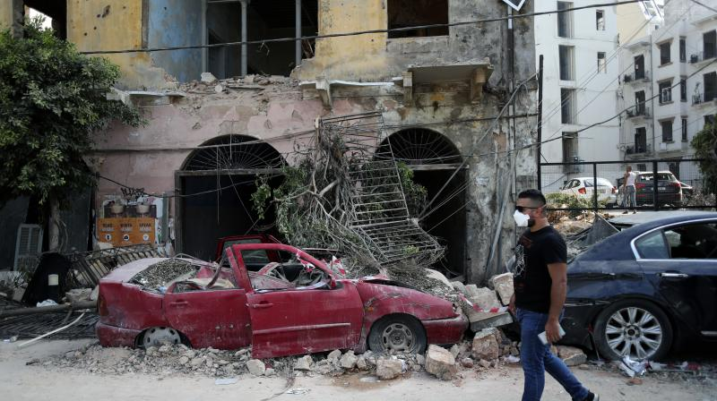 A man walks past a destroyed car at a neighborhood near the scene of Tuesday's explosion that hit the seaport of Beirut, Lebanon. (AP)