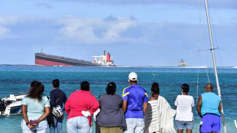 Bystanders look at MV Wakashio bulk carrier that had run aground and from which oil is leaking near Blue Bay Marine Park in south-east Mauritius. (AFP)