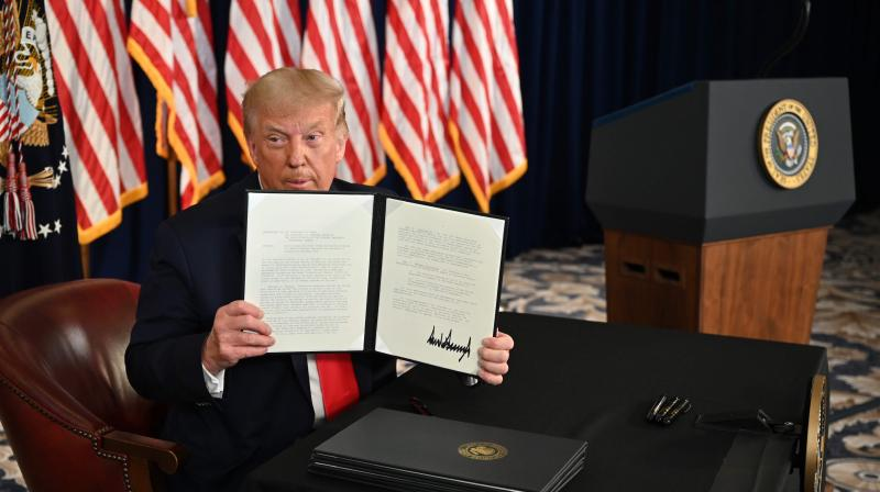 US President Donald Trump signs executive orders extending coronavirus economic relief, during a news conference in Bedminster, New Jersey. (AFP)