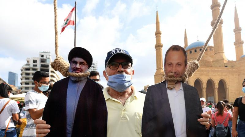A man poses for a picture with a cardboard cut-out of Hassan Nasrallah (L), the head of Lebanon's Shiite Muslim movement Hezbollah, and former Foreign Minister Gibran Bassil hung by Lebanese protesters in downtown Beirut. (AFP)