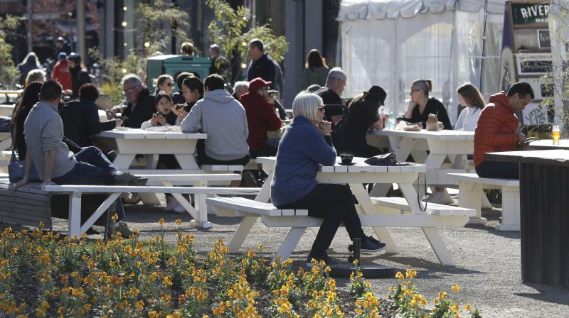 Customers enjoy lunch in the sunshine at the Riverside Market in Christchurch, New Zealand, Sunday, Aug. 9, 2020. New Zealand marked a 100 days of being free from the coronavirus in its communities Sunday, Aug. 9, with just a handful of infections continuing to be picked up at the border where people are quarantined. (AP)