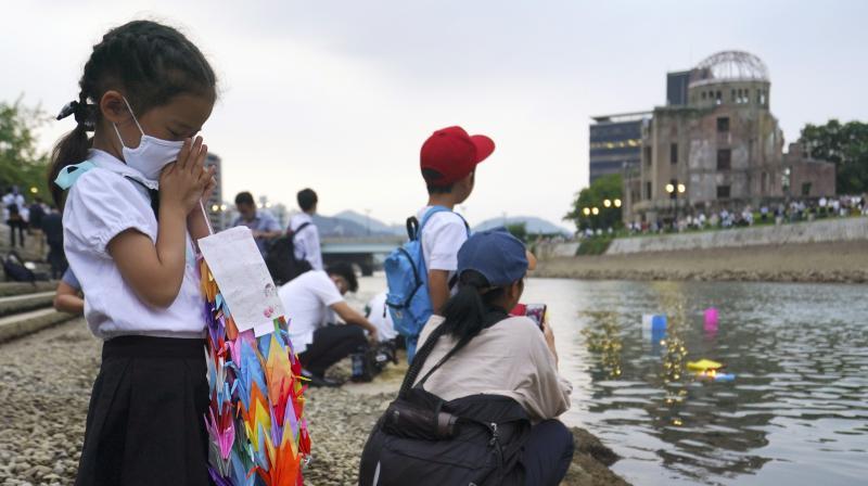 Saki Morioki, 5 years old, prays as paper lanterns float along the Motoyasu River in front of the Atomic Bomb Dome in Hiroshima. (AP)