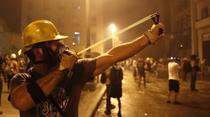 A protester uses a slingshot toward the Lebanese riot police, during anti-government protest following the massive explosion which devastated Beirut, Lebanon. (AP)