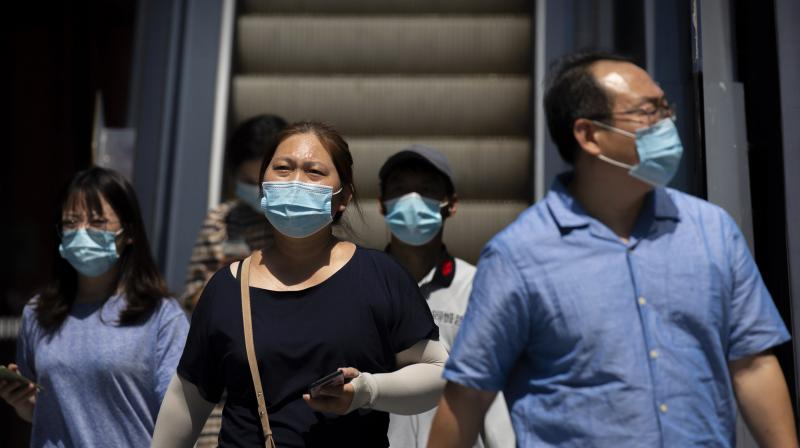 People wearing face masks to protect against the coronavirus walk at a shopping and office complex in Beijing. (AP)