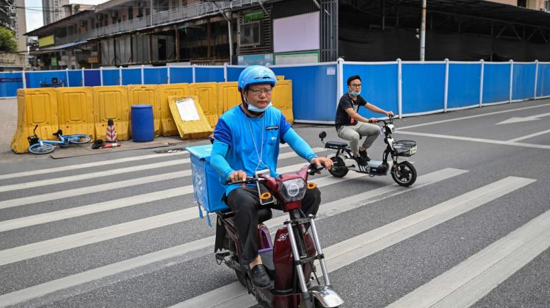 Men riding scooters next to the still-closed Huanan Seafood Wholesale Market in Wuhan in China's central Hubei province. (AFP)