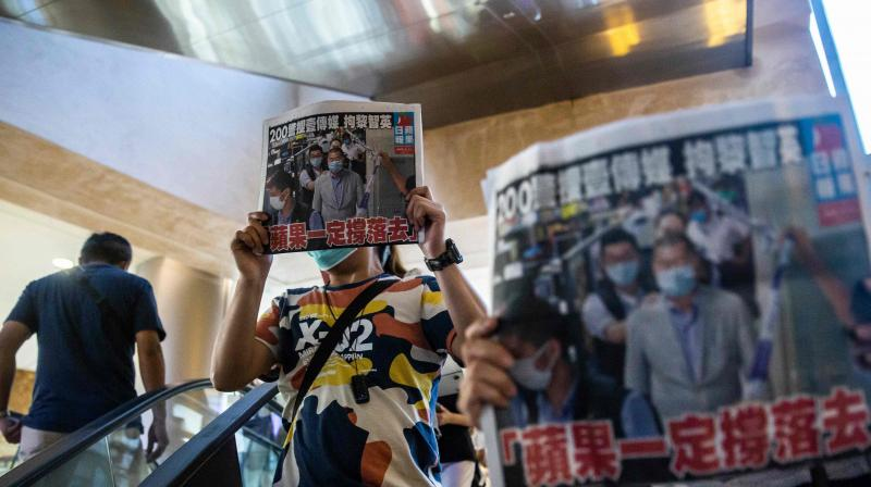 People hold up copies of the Apple Daily as they protest for press freedom inside a mall in Hong Kong on August 11, 2020, a day after authorities conducted a search of the newspaper's headquarters after the company's founder Jimmy Lai was arrested under the new national security law. (AFP)