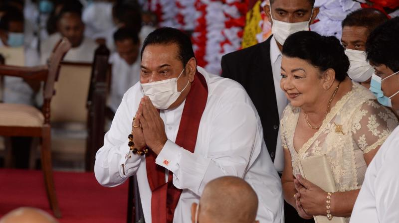 New Prime Minister Mahinda Rajapakse (L) and his wife Shiranthi Rajapaksa (2R) gesture as they arrive for the new cabinet swearing-in ceremony at the Buddhist Temple of the Tooth in the ancient hill capital of Kandy, some 116 km from Colombo on August 12, 2020.(AFP)