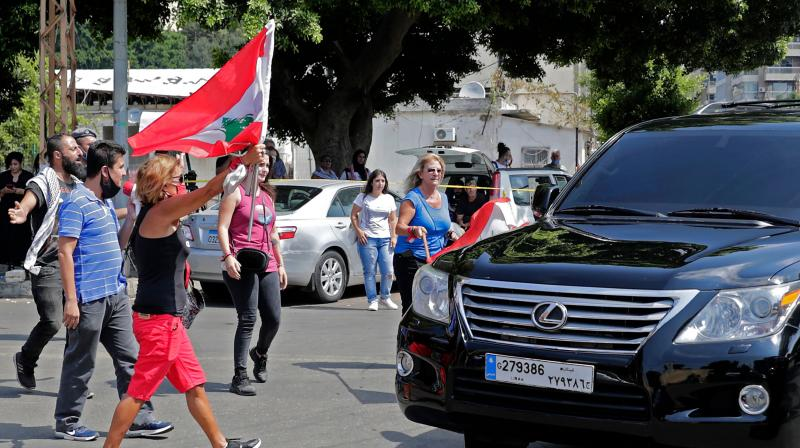 Lebanese anti-government protesters attack a vehicle belonging to a member of the parliament upon his arrival to the parliamentary session at the UNESCO Palace in Beirut. (AFP)