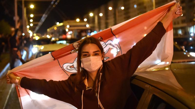 A woman wearing a face mask holds the former white-red-white flag of Belarus during a protest rally against police violence during recent rallies of opposition supporters, who accuse strongman Alexander Lukashenko of falsifying the polls in the presidential election, in Minsk. (AFP)