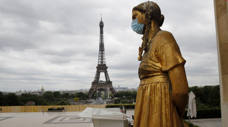 A statue wears a mask along Trocadero square close to the Eiffel Tower in Paris. (AP)