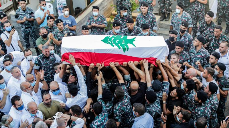 Firefighters carry the coffin of their comrade Ralph Malachi, who was killed in the monster explosion at the port of Beirut and whose remains were recently found and identified, draped in the Lebanese national flag, during a funerary ceremony at the civil defence headquarters in the Karantina (La Quarantaine or Quarantina) neighbourhood of the capital just by the ravaged port. (AFP)