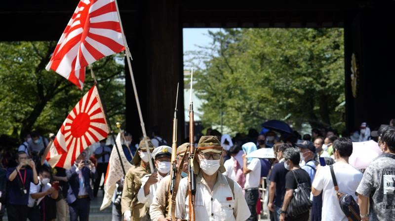 Visitors in Japanese Imperial army and navy uniforms walk near Yasukuni Shrine, which honors Japan's war dead. (AP)