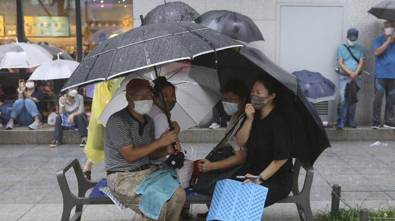 People wearing face masks hold umbrellas in the rain in Seoul, South Korea. (AP)