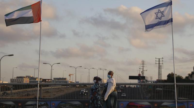 Women wearing face masks against the coronavirus walk past United Arab Emirates and Israeli flags at the Peace Bridge in Netanya, Israel. (AP)