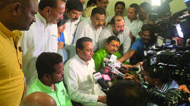 Kamal Nath being flanked by two rebel BJP MLAs in a press conference.