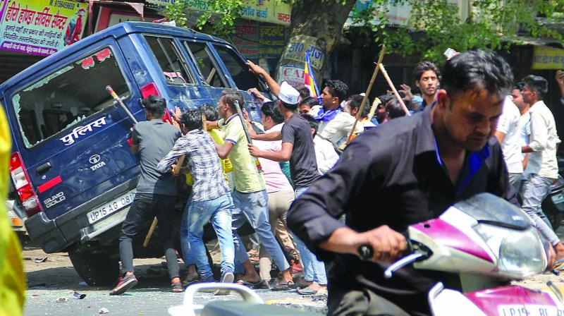 Dalit protesters blocked trains, clashed with police and set dozens of vehicles ablaze in several states during a nationwide bandh.