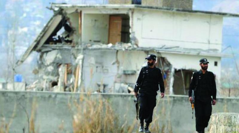 Pakistani policemen outside the Abbottabad building where Osama bin Laden was killed by US special forces in May 2011.
