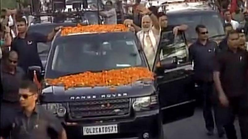 PM Modi waves at supporters as he proceeds towards the venue of BJP National Executive Meet in Bhubaneshwar. (Photo: Twitter | ANI)