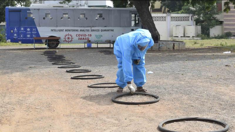 Sanitation employee adjust the tyres for distance maintenance before starting Swab tests due to COVID0-19 at Bishop Grassi school in Vijayawada. (DC Image:Narayana Rao)