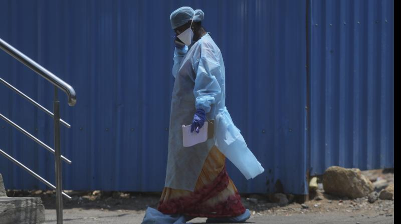 A health worker walks inside a containment zone to collect details during lockdown to prevent the spread of new coronavirus in Hyderabad. AP Photo