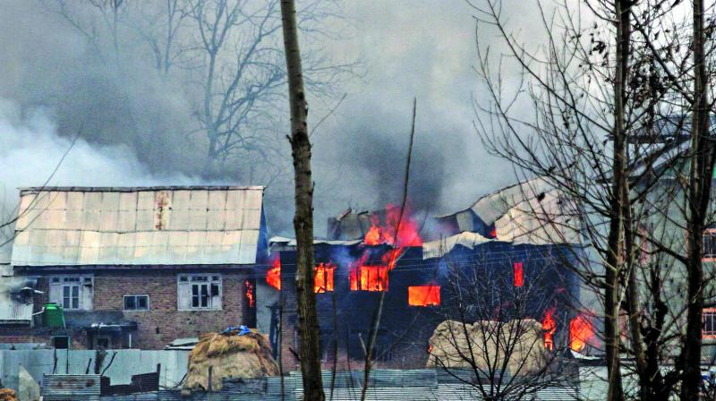 A house in which militants are suspected to have sheltered is in flames after a gunfight between militants and the security forces in South Kashmir's Pulwama district, some 10 km away from the spot of the recent suicide bombing. (Photo; AFP)