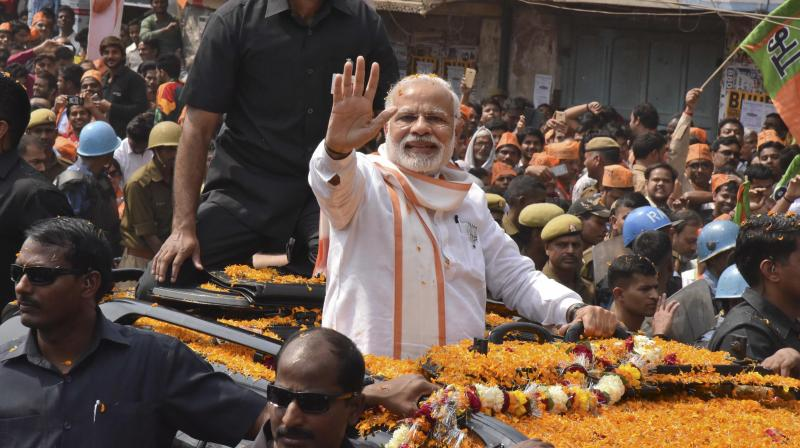 Prime Minister Narendra Modi waves to supporters as he campaigns for his party in the Uttar Pradesh state elections in Varanasi. (Photo: PTI)