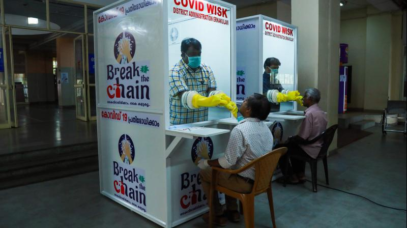 Medical staff collect samples from people at a walk-in sample kiosk (WISK) to test for the COVID-19 coronavirus at the Ernakulam Medical College in Kerala. (AFP)