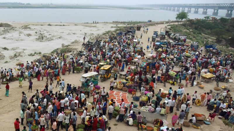 People violate social distancing guidelines as they purchase vegetables, during the nationwide lockdown to curb the spread of coronavirus, at Digha ghat in Patna. PTI photo
