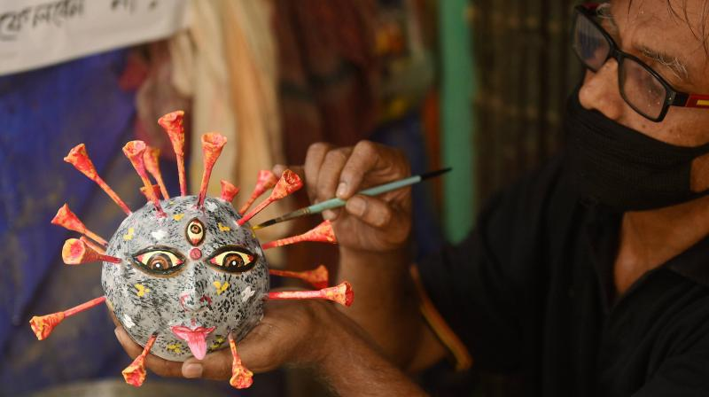 An artist makes a coronavirus themed idol for Puja festivities at a workshop at Kumartuli in Kolkata. PTI photo