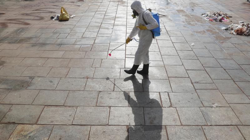 A member of the National Disaster Response Force sprays disinfectant as a precautionary measure against the spread of the COVID-19 virus at Charminar in Hyderabad on March 22, 2020. India is observing a 21-day lockdown to break the chain of transmission of the virus. (AP)