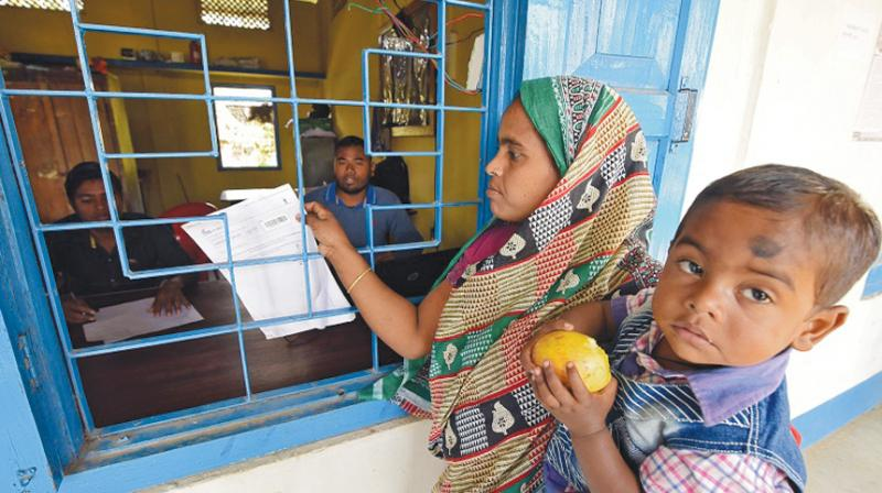 A woman checks her name on the final draft of the state's National Register of Citizens after it was released, at an NRC Seva Kendra, in Morigaon. (Photo: File)
