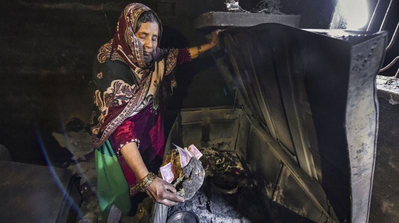A woman shows the remains of her savings burnt in the recent violence in Delhi. (PTI)