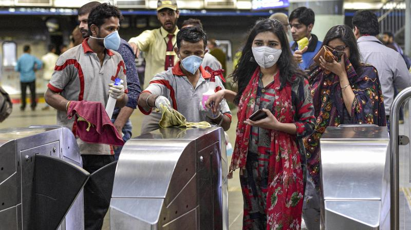 Workers clean the entry gates at Rajeev Chowk metro station in the wake of the novel coronavirus (COVID-19) outbreak in New Delhi, Friday, March 13, 2020. India has more than 80 positive coronavirus cases so far. (PTI)
