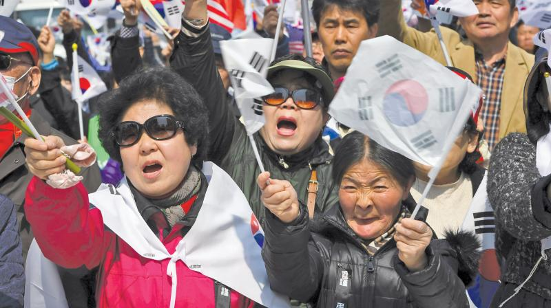 Supporters of South Korea's impeached ex-President Park Geun-Hye wave national flags during a rally demanding a repeal of the impeachment in Seoul on March 18. (Photo: AFP)