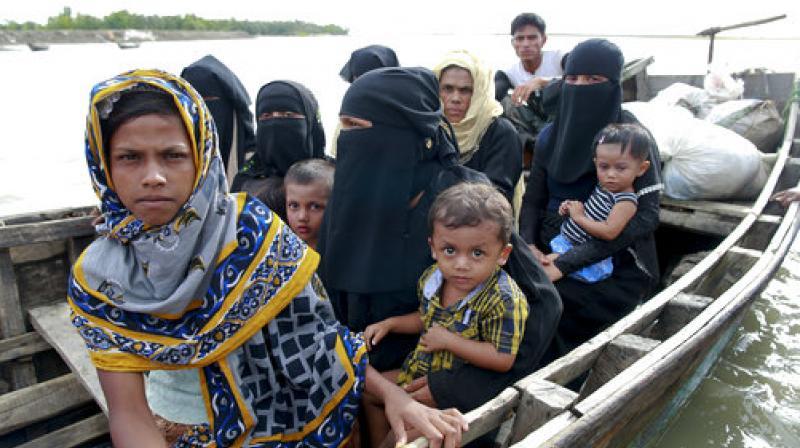 Members of Myanmar's Muslim Rohingya minority sit in a boat to cross a canal at Shah Porir Deep, in Teknak, Bangladesh. (Photo: AP)