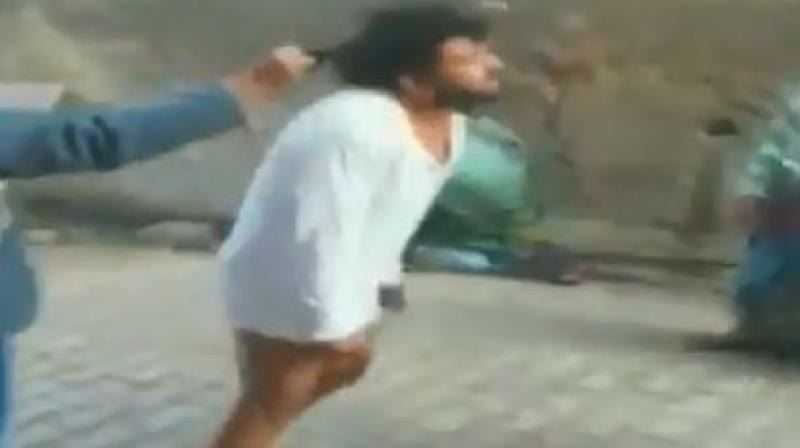 The video shows women beating up the priest who, in a white kurta and with bare legs, tries to defend self. (Photo: Twitter | Screengrab)