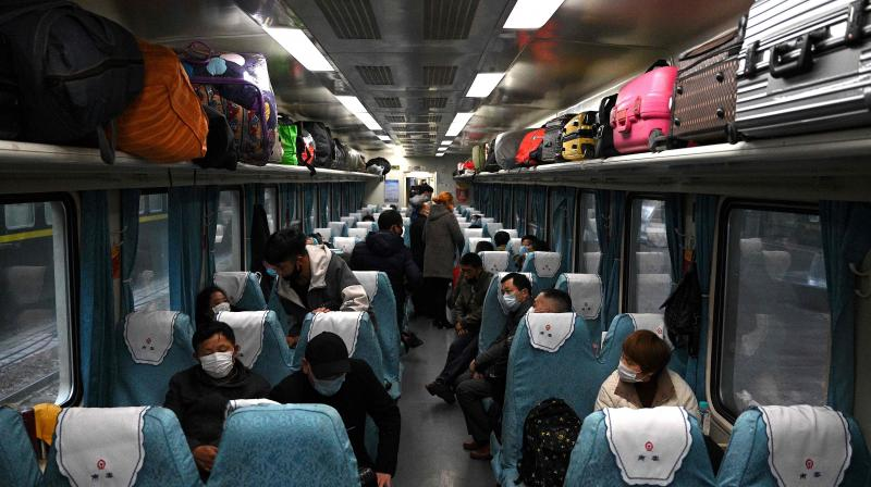 Passengers wearing facemasks sit inside a train at Nanjing railway station in Nanjing, the capital of China's eastern Jiangsu province. AFP Photo