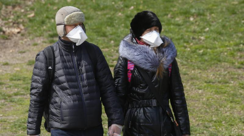 A couple wears face masks and surgical gloves as they walk in Central Park in New York City. AP Photo