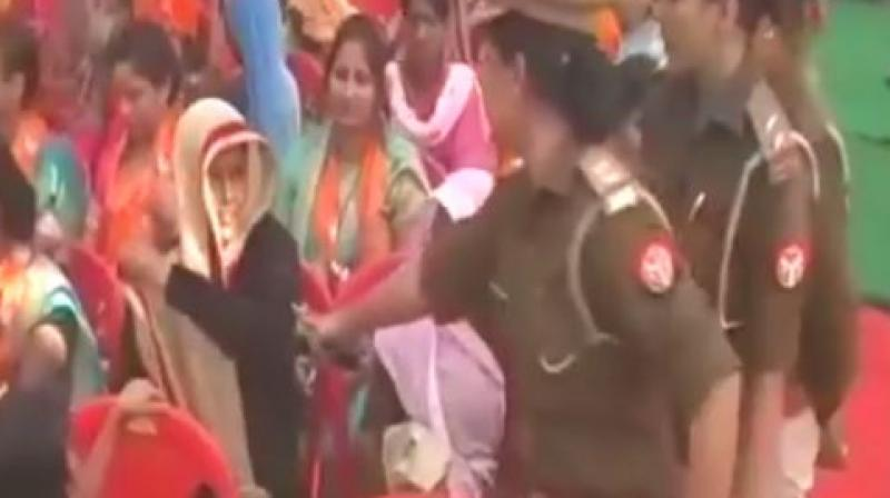 A video showing the woman taking off her black burqa minutes before the chief minister makes an appearance at the rally on Tuesday has gone viral. (Photo: ANI/Screengrab)
